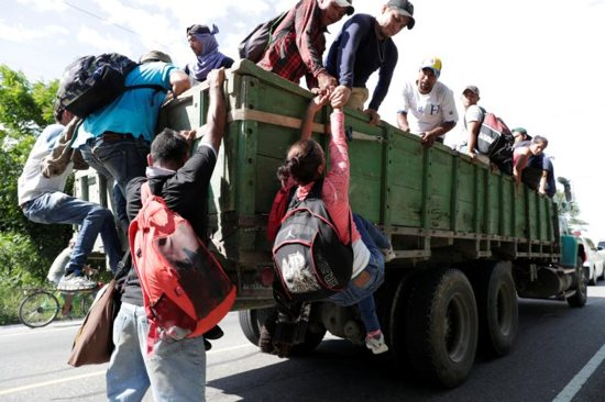 Honduran migrants climb on a truck Oct. 23 in Chiquimula, Guatemala, as they travel with other Central Americans in a caravan heading to the United States.