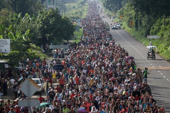 A large caravan of migrants from Central America, trying to reach the U.S., walk along a road Oct. 21 in Hidalgo, Mexico.