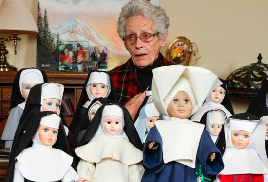 Margaret Alsup of Cumming, Ga., stands behind some of the 75 nun dolls Dec. 21, 2017, that she collected over the years. All of the dolls, which are clothed in authentic habits, have been donated to the Archdiocese of Atlanta's Office of Archives and Records.