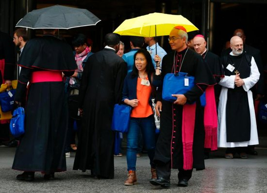 Indonesian youth delegate Anastasia Indrawan share an umbrella with an unidentified bishop as they leave a session of the Synod of Bishops on young people, the faith and vocational discernment at the Vatican