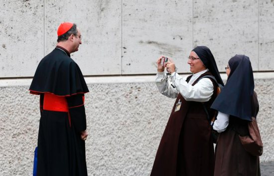 A nun takes a video of Cardinal Sergio da Rocha of Brasilia, Brazil, relator of the Synod of Bishops on young people, the faith and vocational discernment, after a synod session at the Vatican Oct 5.