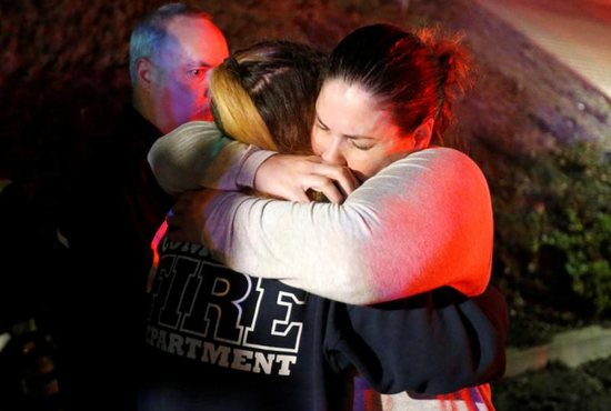 A woman who fled the Borderline Bar and Grill is embraced by a first responder Nov. 8 outside the Borderline Bar and Grill in Thousand Oaks, Calif., after a gunman killed at least 13 people. The gunman, who opened fire without warning late Nov. 7, was found dead inside the establishment, authorities said.