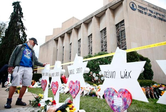 A man takes a moment at each of the Star of David memorials Oct. 29 with the names of the people who were killed at the Tree of Life Synagogue in Pittsburgh.