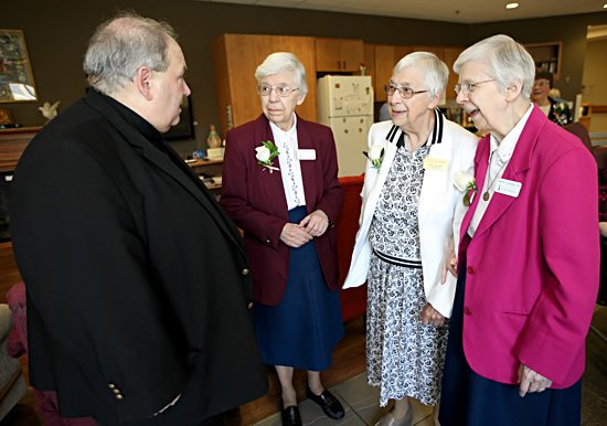 Archbishop Bernard Hebda talks with Benedictine Sisters Andriette, left, Rosella and Andrine Schommer June 22 after celebrating Mass to mark the 70th anniversary of St. Paul's Monastery in Maplewood.