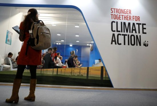 A woman watches an exhibition inside the venue of the U.N. climate change conference, or COP24, Dec. 8 in Katowice, Poland.