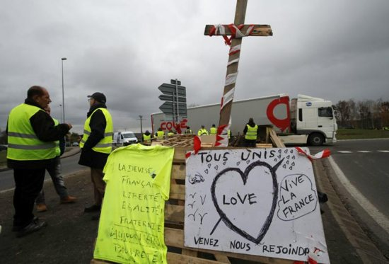 Protesters wearing yellow vests, the symbol of a French drivers' protest against higher diesel fuel taxes, occupy a roundabout Dec. 6 in Gaillon, France.
