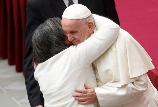A woman embraces Pope Francis as he arrives to lead his general audience in Paul VI Hall Dec. 12 at the Vatican.