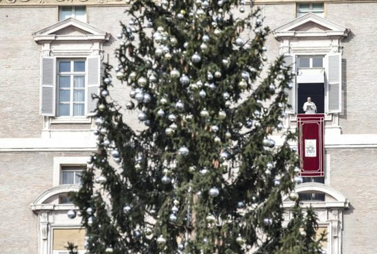 """The Christmas tree is seen as Pope Francis leads the Angelus prayer from the window of his studio overlooking St. Peter's Square at the Vatican Dec. 2. The pope lit an Advent candle as he launched the Christmas campaign, """"Candles for Peace in Syria,"""" an initiative of Aid to the Church in Need."""