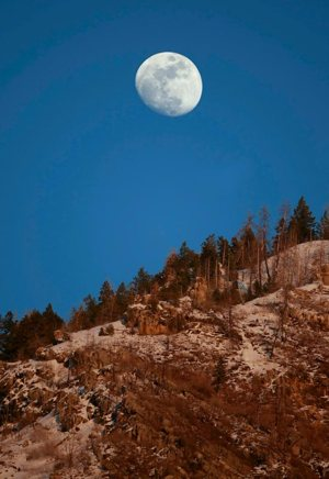 As the evening sun sets on Y Mountain, the moon rises above the tree line near Provo, Utah. The congressionally mandated Fourth National Climate Assessment, released Nov. 23 by the White House, projects that climate change will cost the country hundreds of billions of dollars a year by 2090.