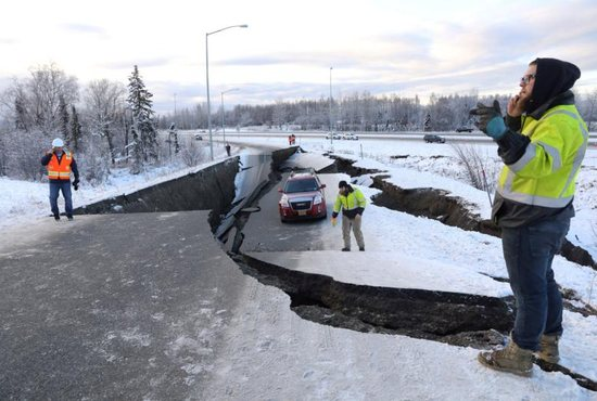 First responders stand on a collapsed roadway near the airport after a magnitude 7.0 earthquake Nov. 30 in Anchorage, Alaska.