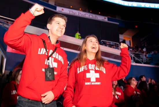 "At the Archdiocese of Washington's Jan. 18 Youth Rally for Life at the Capital One Arena, Matteo Caulfield and Caroline Rotkis, seniors from Benet Academy, a Benedictine school in Lisle, Ill., join fellow students from their school in wearing matching red hooded sweat jackets with the words ""LIFE GUARD"" emblazoned on the front. They had made a 15-hour bus ride to attend the rally, Mass and March for Life."