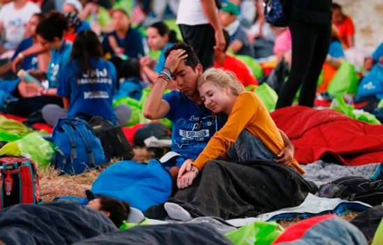 A couple wake up before Pope Francis' celebration of Mass for World Youth Day pilgrims at St. John Paul II Field in Panama City Jan. 27, 2019.