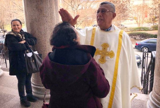 Father Estefan Turcios, head of the human rights office for the Archdiocese of San Salvador, blesses a parishioner Dec. 30, 2018, after Mass at the Shrine of the Sacred Heart in Washington. Salvadorans and admirers of St. Oscar Romero can honor the Salvadoran saint's life by learning about him and then helping those on the margins the way he did, said Father Turcios, director of Pontifical Missions for El Salvador, during a brief visit to Washington.