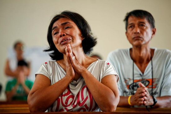 A woman prays during Mass at a church in Tacloban, Philippines, Nov. 17, 2013. The Philippines, with about 80 million Catholics, is the epicenter of the church in Asia and has seen more public cases of sexual abuse against both minors and women and in recent years than other Asian countries.