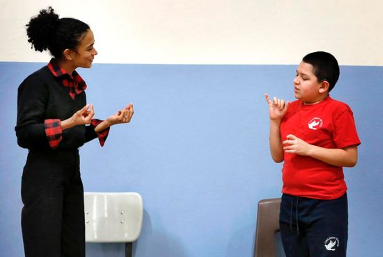 "Anthony Zuniga, a fifth-grader at Children of Peace Catholic in Chicago, asks Lauren Teruel Ridloff a question using sign language Feb. 22, 2019. The actress, who is deaf, is a Tony Award nominee and currently a star of ""The Walking Dead"" series on AMC. She graduate in 1991 from the school, which was then called Holy Trinity School for the Deaf."
