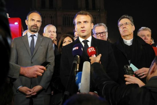 French President Emmanuel Macron speaks to the media alongside Prime Minister Edouard Philippe, left, and Paris Archbishop Michel Aupetit, outside Notre Dame Cathedral April 16, 2019, after a fire broke out in the iconic Paris structure. Officials said the cause was not clear, but that the April 15 blaze could be linked to renovation work.