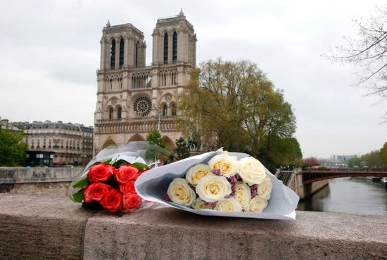 Flowers are seen on the ledge of a bridge near Notre Dame Cathedral April 16, 2019, after a fire broke out in Paris. Officials said the cause was not clear, but that the April 15 blaze could be linked to renovation work.