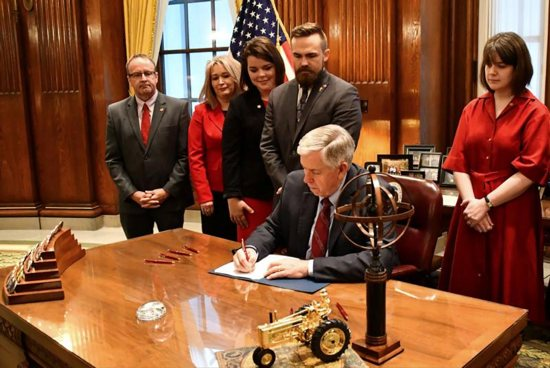 """Missouri Gov. Mike Parson signs a bill into law banning abortion beginning in the eighth week of pregnancy, alongside state House and Senate members and pro-life coalition leaders at his office in Jefferson City May 24, 2019. Archbishop Joseph F. Naumann of Kansas City, Kan., chairman of the U.S. bishops' Committee on Pro-Life Activities, in a May 23 statement praised Missouri and other states for passing pro-life legislation in recent weeks. """"Every single human life has value,"""" he said."""