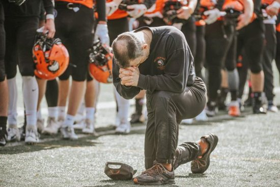A coach kneels in prayer Oct. 13, 2018, during a high school game at Hurley Field in Berkeley, Mich. As part of a new pastoral note encouraging Catholics in the Archdiocese of Detroit to keep Sunday as a day of holiness, rest and family togetherness, Archbishop Allen H. Vigneron introduced a new policy requiring Catholic parishes and schools to stop scheduling athletic games and practices on Sundays.