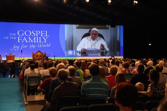 """Attendees watch Pope Francis on a screen during the opening ceremony of the World Meeting of Families in Dublin Aug. 21, 2018. The Vatican announced the theme Pope Francis has chosen for the next World Meeting of Families, which will be in Rome June 23-27, 2021: """"Family love: a vocation and a path to holiness."""""""