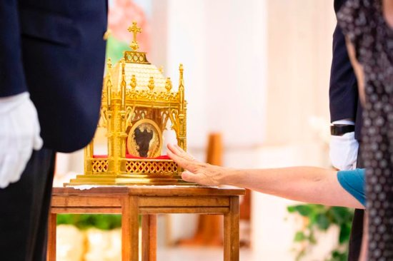 A worshipper venerates a reliquary containing St. John Vianney's incorrupt heart at St. Anne Church in Gilbert, Ariz., May 6, 2019.
