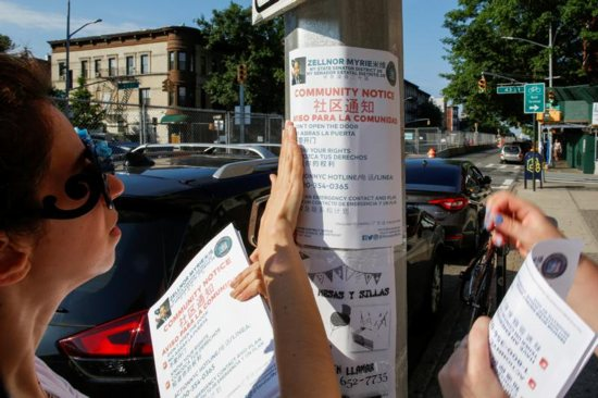 Community members in Brooklyn, N.Y., tape immigration information to a pole