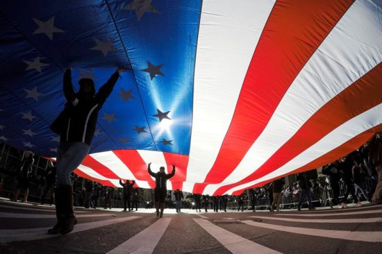 People in New York City carry the U.S. flag
