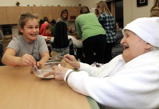 A religious sister shares a laugh with a girl at the Sorrowful Mother retirement home in Oshkosh, Wis.
