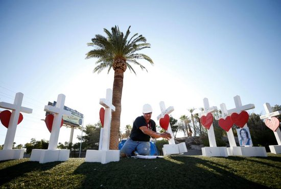 Greg Zanis of Aurora, Ill., works on a wooden cross memorial