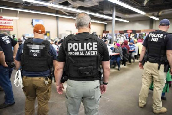 U.S. Immigration and Customs Enforcement officers look on after executing search warrants and making some arrests