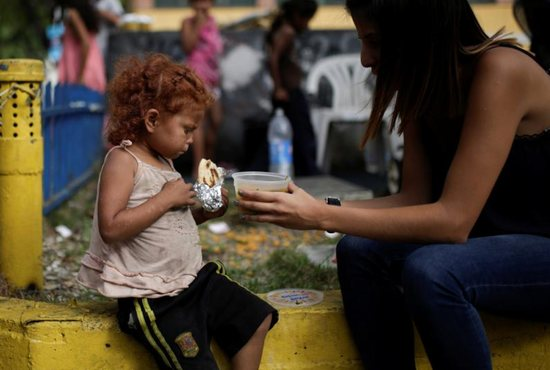 "A volunteer with ""Make the Difference"" charity initiative gives a cup of soup and an ""arepa"" to a homeless child along a street in Caracas"