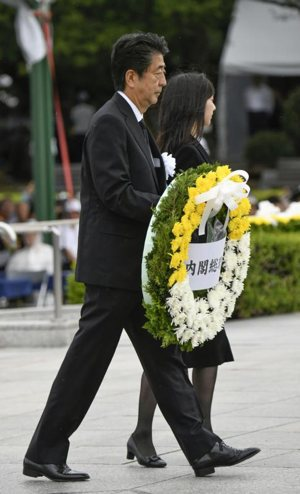 Japanese Prime Minister Shinzo Abe carries a wreath for the victims of the 1945 atomic bombing