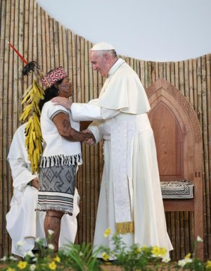 Pope Francis is greeted by a member of an indigenous group from the Amazon region