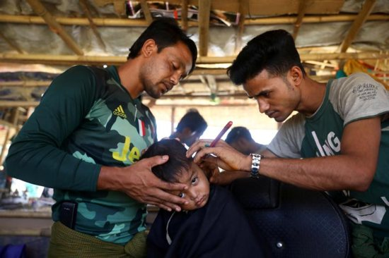 A Rohingya refugee boy has his hair cut at a refugee camp