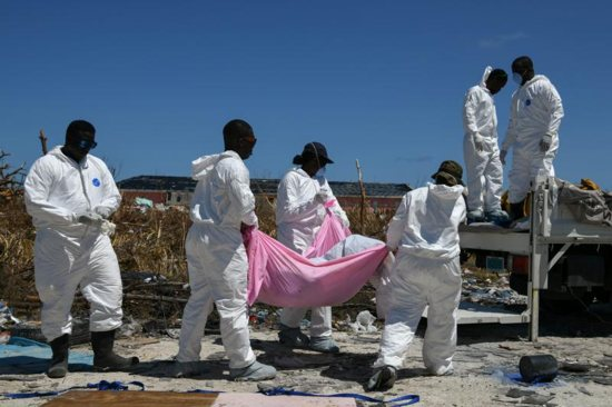 Personnel from the Royal Bahamas Police Force remove a body recovered in a destroyed neighborhood