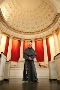 Father Linus DeSantis, OFM Conv., stands in Syracuse University's Hendricks Chapel.  (Photo by Riley Woods Photography)