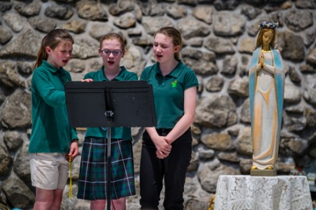 Sixth greaders (from left) Monica Link, Kira Jones, and Ashlyn Lancki lead students from All Saints School in Endicott in a hymn at the Marian Shrine at St. Joseph Church May 12 after the crowning the Blessed Mother with flowers. (Sun photo | Chuck Haupt)