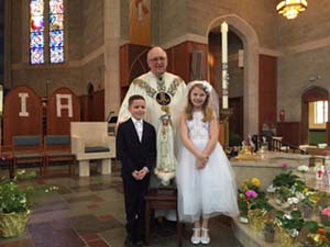Blessed Sacrament School's second-grade First Communicants crowned the Blessed Mother May12 at a morning liturgy.Pictured with Father Peter Reddick are Joseph Wesley Calangelo Amiah Emig. -Photo courtesy Blessed Sacrament School