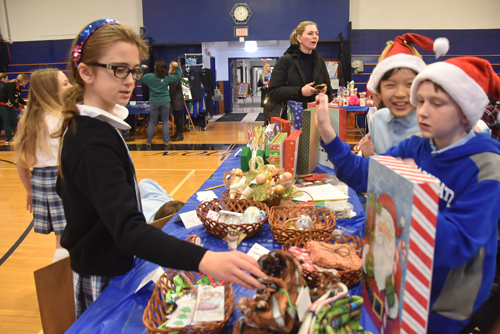 Fourth-grader Caitlin Barrett looks over the handmade merchandise offered by fifth- graders Eric Lee, left, and Nicholas Chmelicek. (Photos courtesy Caroline A. Calimlim)