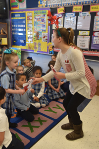 Immaculate Conception School sixth-grader Audrey Schaefer hands a treat to kindergartner Lilah Kennedy.