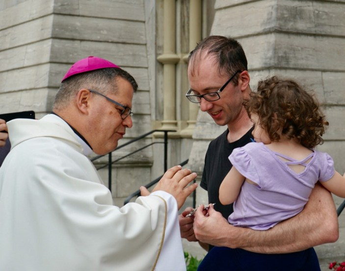 Bishop-elect Lucia blesses Bennett McLoughlin and daughter Emeline following Mass at the Cathedral of the Immaculate Conception