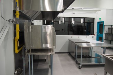 a kitchen with stainless steel tables and hood vent with gas-fired equipment