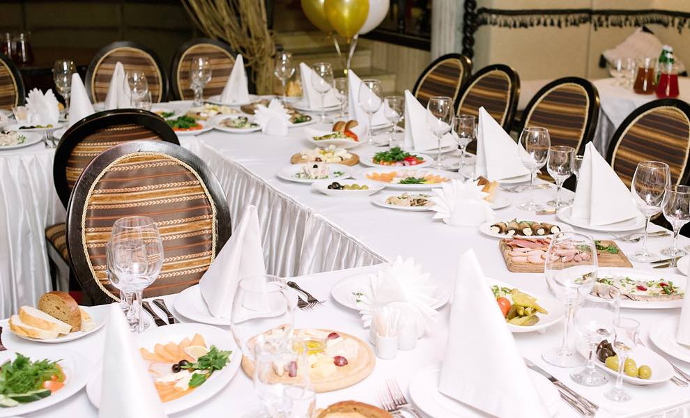 classy birthday dinner table with wooden chairs and white tablecloth with white table settings