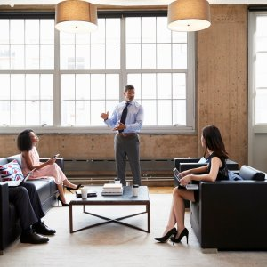 Male manager presenting at informal meeting in a lounge room