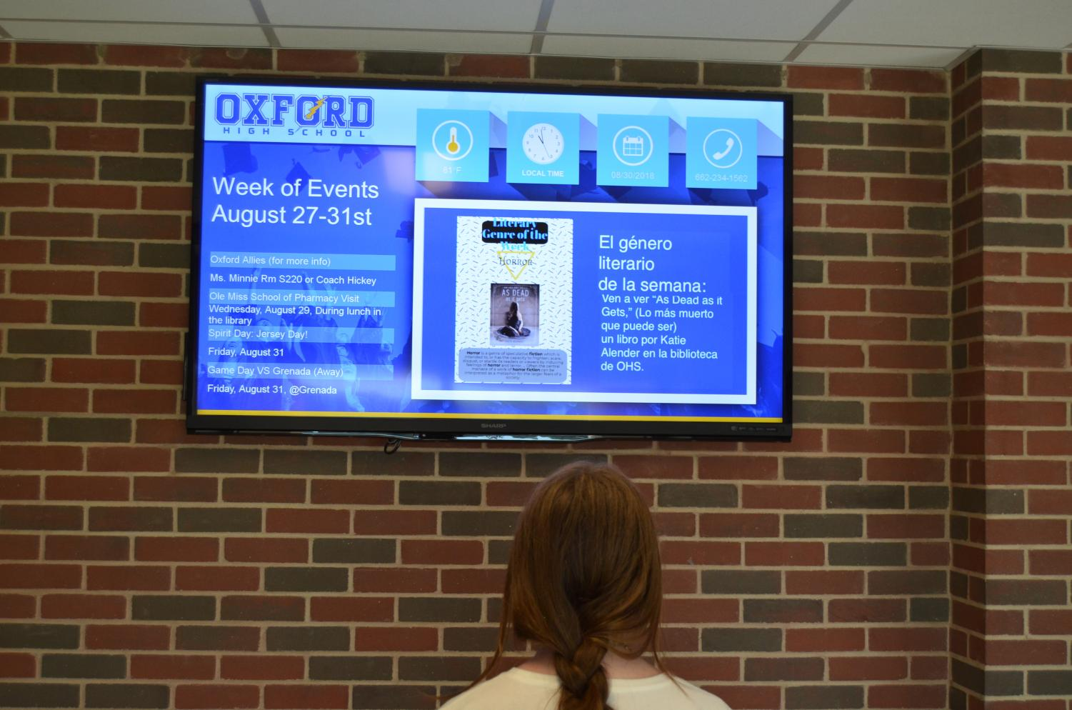 A student looks at the translated version of the school announcements on the televisions in the hallway. Spanish teacher Emily Maples has been working to implement more Spanish translations throughout the school.