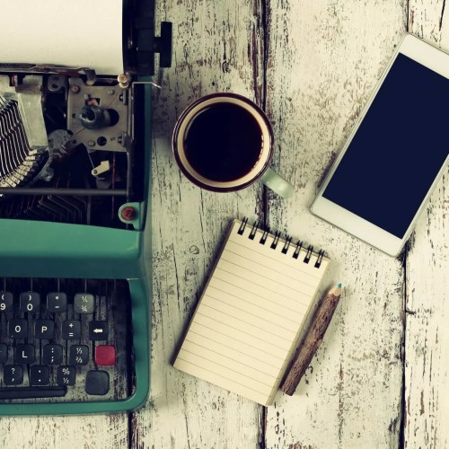 retro filtered image of vintage typewriter, blank notebook, cup of coffee and smartphone on wooden table