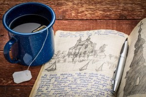 travel or expedition journal - handwriting and drawing in pencil in a notebook against rustic picnic table with cup of tea