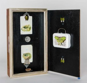 "Soul RetrivaI II 2016, by Thea Fiore-Bloom. Assemblage/mixed media: vintage cigar box, crystal, spark plugs, foreign coins, beetle, Barbi suitcase, 4''x 5''x 9' closed'.  Copyright © 2016 Thea Fiore-Bloom. Used by permission of the artist. <a href=""https://www.etsy.com/shop/EnchantedMuseum"">Click here to visit my Etsy Shop.</a>"
