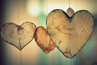 artist made rough edged wooden hearts hanging on wires.