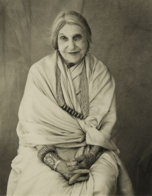 Portrait of Beatrice Wood in a silk sari with great Indian jewelry, smiling serenely.